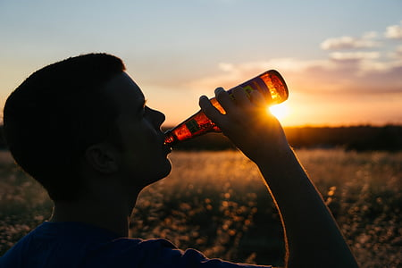 person drinking brown translucent glass bottle