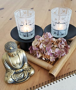 gold-colored Buddha figurine beside purple withered hydrangea flowers and two frosted glass candle holders
