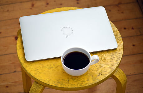 black coffee filled white cup and MacBook Air on top of brown wooden table