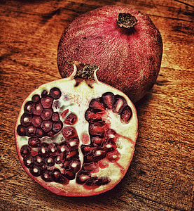 red sliced pomegranate on brown wooden surface