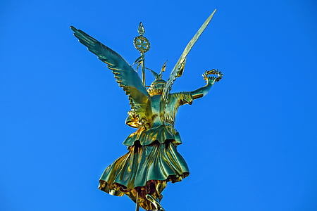 photo of gold-colored statue under blue sky at daytime