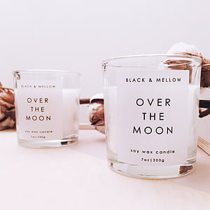 selective focus photographyof two Over the Moon votive candles