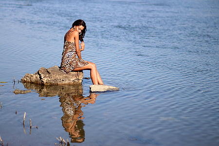 woman sitting on gray rock with feet in water