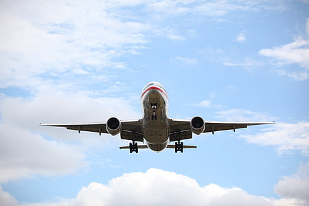 gray and red airplane at clear blue sky