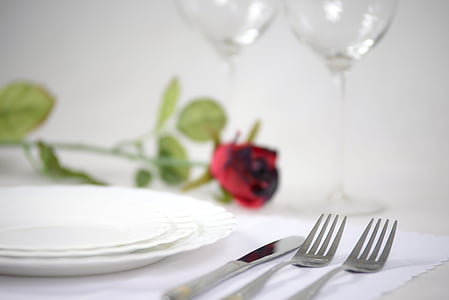 three round white ceramic plates near silver bread knife and two forks