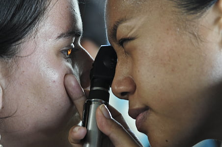 person lighting woman's eye
