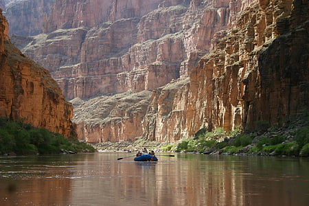 person riding on boat between mountains