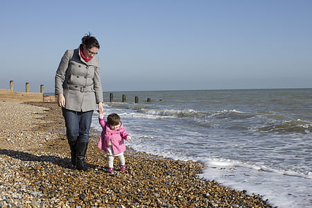 woman in grey double-breasted coat and toddler in pink jacket walking hand-in-hand at beach at daytime