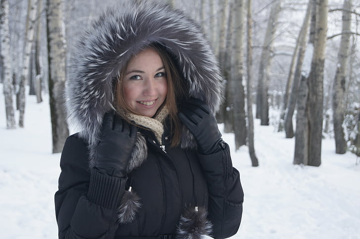 smiling woman wearing parka coat near bare trees over snow ground