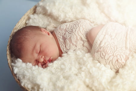 baby in white bed sheet