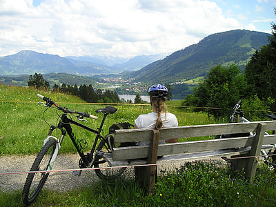 woman in white top sitting beside on bench beside bicycle