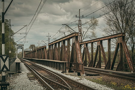 rusted brown metal bridge with train rails under cloudy sky during daytime