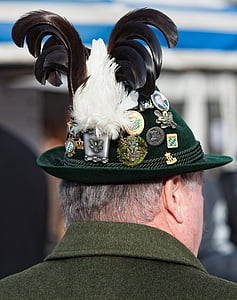 close-up photography of man's green hat and assorted badges