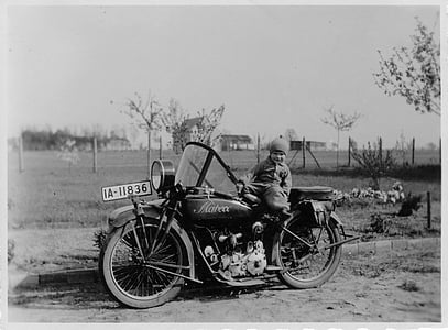 grayscale photo of boy riding motorcycle