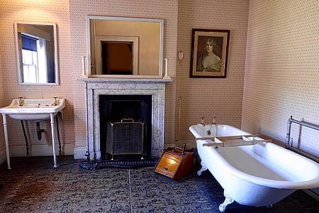 white clawfoot bathtub near fireplace