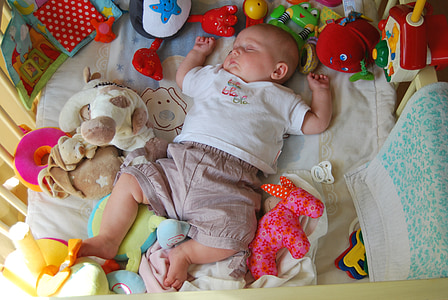 baby sleeping while surrounded by toys