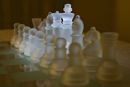frosted glass chess piece set on chessboard