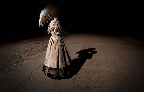 woman in gray dress holding umbrella while standing on concrete floor during nighttime