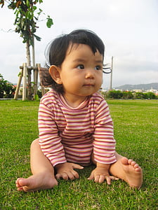 toddler's sitting on grass