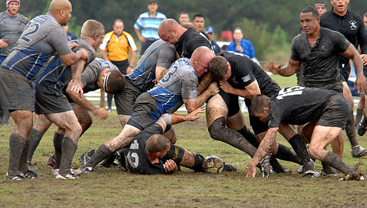 group of men playing rugby on mud field at daytime