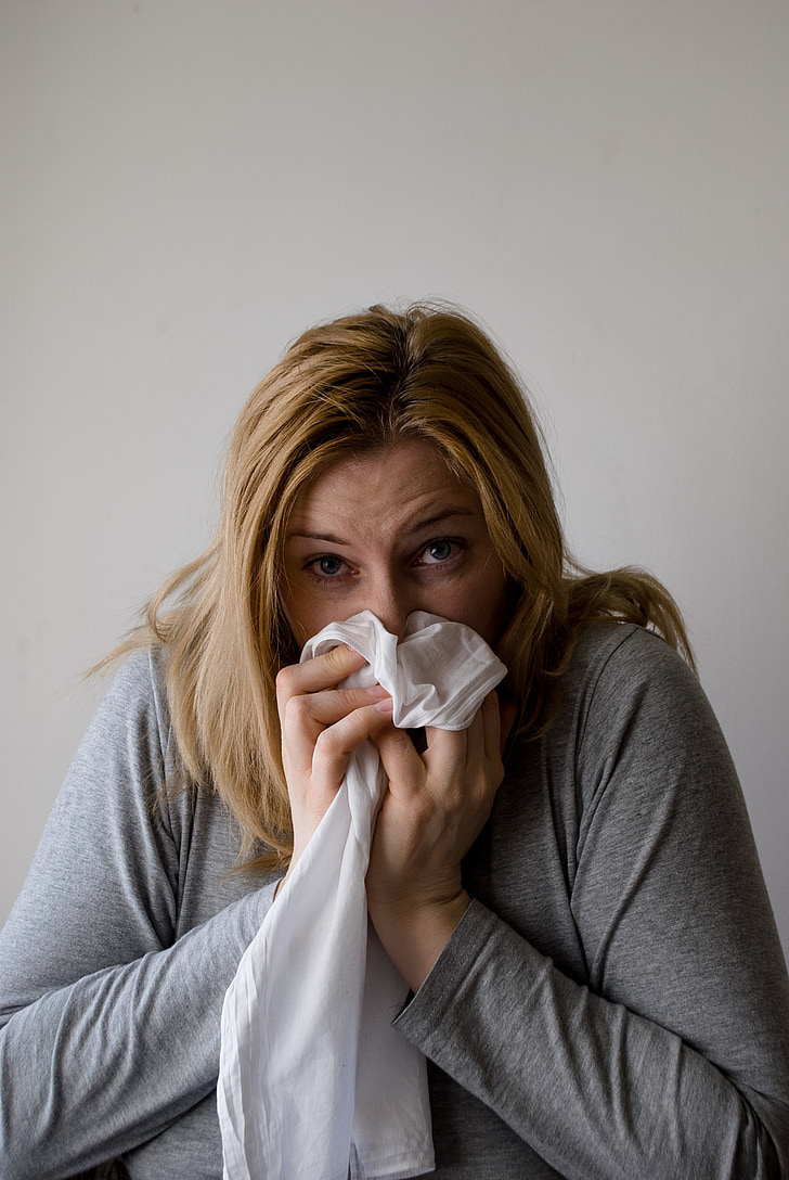woman sneezing on white textile