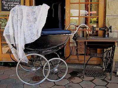 photo of pram stroller beside threadle sewing machine