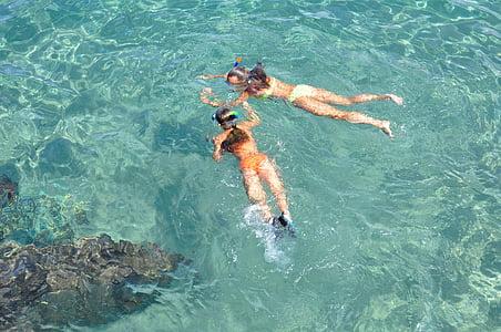 two women swimming on beach