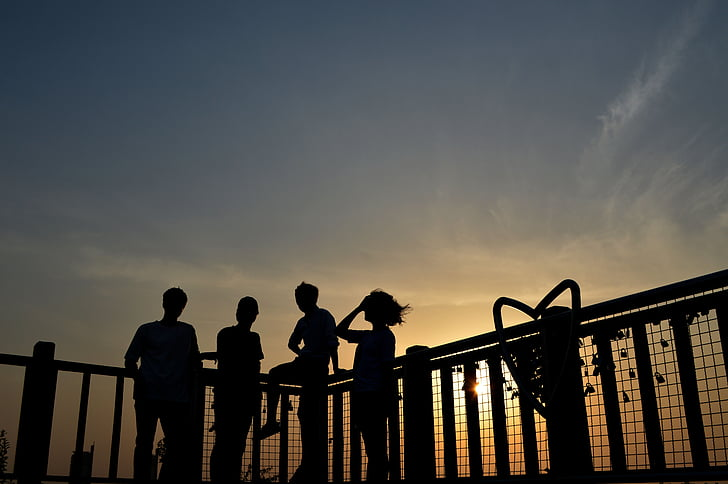 silhouette of four people beside fence during sunset