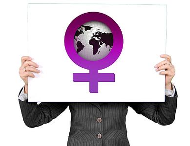 person wearing gray blazer holding globe board