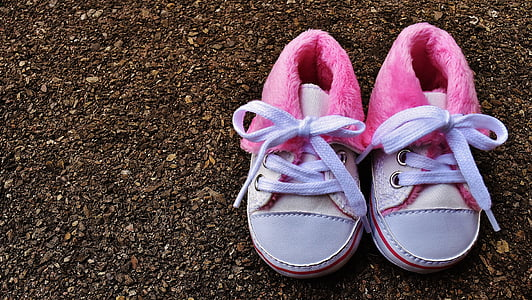 children's pair of pink-and-white shoes on ground