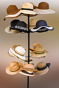 assorted hats hanging on tower rack
