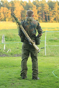 man carrying rifle standing near fence