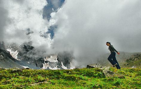 woman wearing grey jacket walking on grass field
