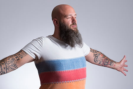 man with tattoos wearing shirt spreading his arms