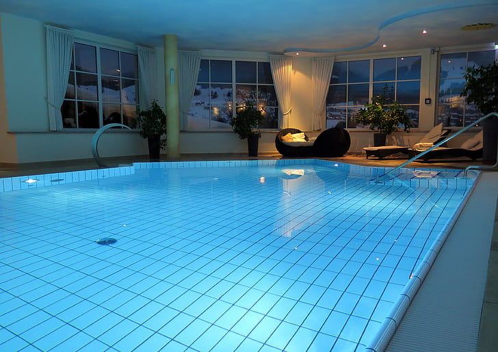 indoor below-ground swimming pool with blue lights during nighttime