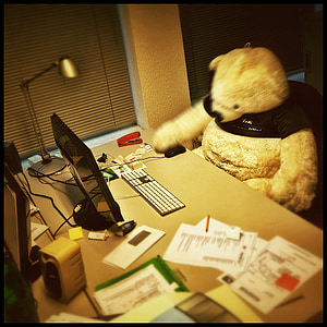 bear plush toy at rolling chair in front desk