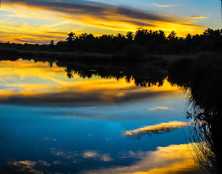photography of lake near trees at sunset