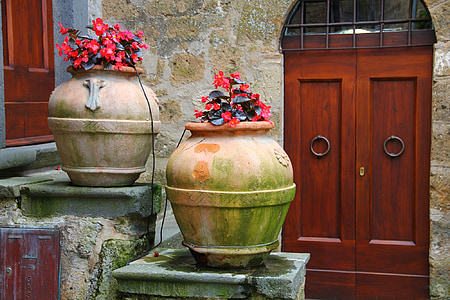 two mossy brown pots with red flowers
