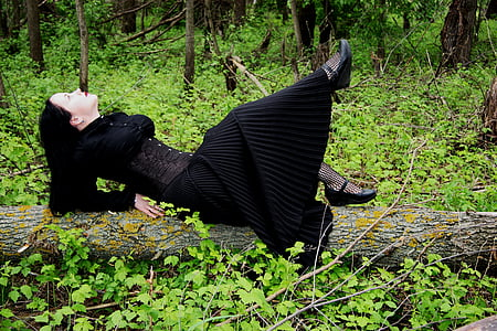 woman in black long-sleeved dress laying on tree trunk