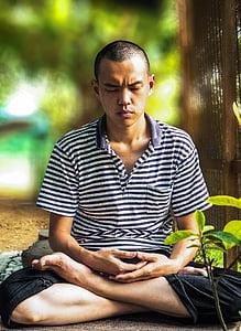 man meditating beside tree