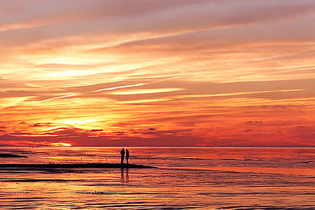 silhouette of two persons beside sea during sunset