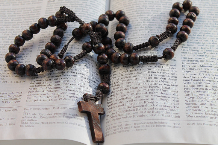 brown rosary on opened bible