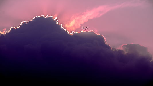 airplane silhouette above clouds during golden hour