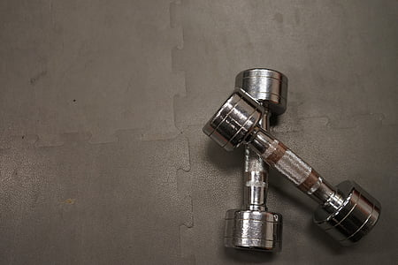 pair of grey fixed weight dumbbells on grey puzzle mat