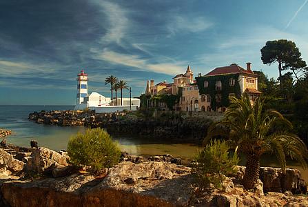 white light house near to mansion overlock the ocean