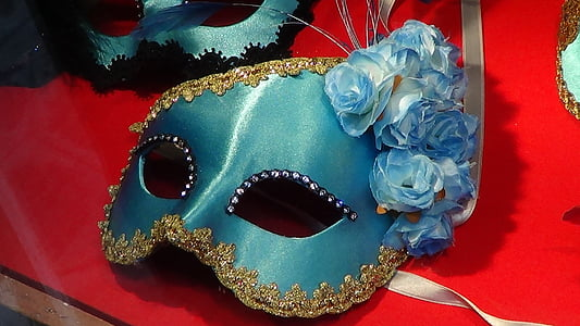blue masquerade mask on top of red table