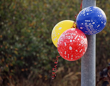 yellow, red, and blue balloons beside metal pipe