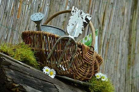 gray steel watering can in brown wicker basket