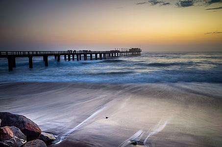 brown dock in seashore painting