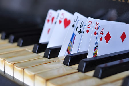 close up photography of playing cards put in between piano keys